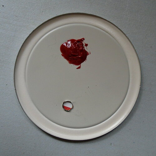 Bottom-view of the metal lid of a canning jar with a red blob of silicone and a small hole. Red and whote Tyvek is visible through the hole